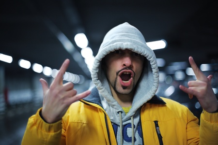 intimidating: Portrait of young man in hoodie showing intimidating gesture. Shallow DOF.