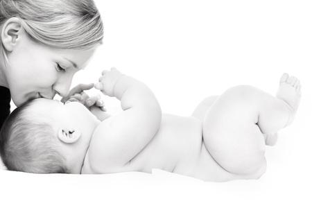 madre y bebe: Feliz madre besando la ni�a sobre fondo blanco Foto de archivo