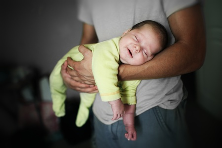 Newborn baby girl sleeping in fathers arms.