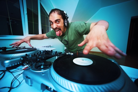 Crazy DJ Scratching on the Turntables at house party Stock Photo