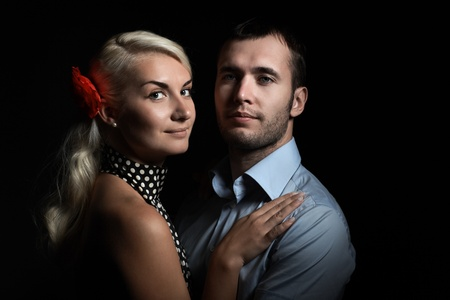Portrait of young couple in love together on dramatic black background. photo