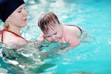 Mother teaching baby to swim in water pool photo