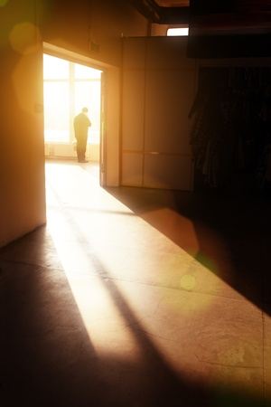 Silhouette maschile nel vuoto interiore alla ricerca nella finestra, illuminata da luce solare drammatica.