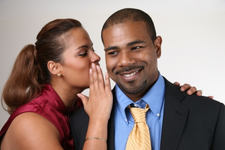 Woman whispering in husbands ear. Closeup, shallow DOF, focus on man. photo