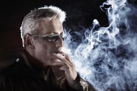 Man smoking cigarette at night, closeup.
