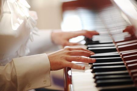 女性の遊ぶピアノを手します。クローズ アップ、浅い何も知らない。