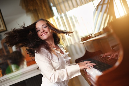 keyboard player: Happy young woman playing piano indoors. Closeup, shallow DOF.