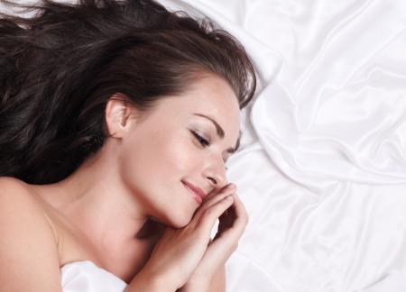 Portrait of beautiful woman lying on white silk bed, closeup.
