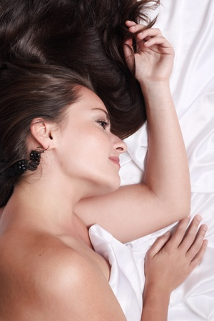 Portrait of beautiful woman lying on white silk bed, closeup. photo