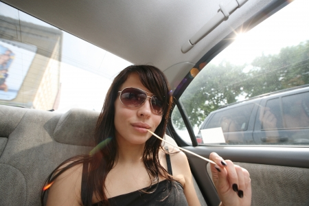 Young brunette woman in sunglasses in car. Wide angle view. photo