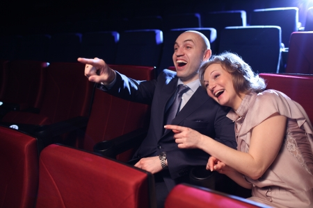 Young couple in cinema movie theater laughing while watching comedy show.