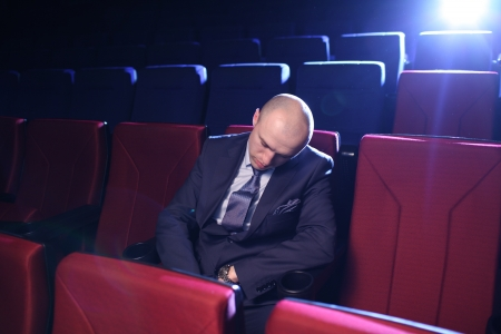 Bald man sleeping in empty movie theater.