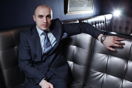 Portret van knappe kale business man in pak in luxe interieur.