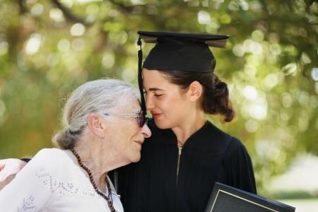 licenciado: Graduado feliz con la graduaci�n de selebrating de grandomther. Closeup, DOF superficial. Foto de archivo