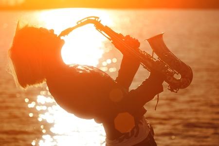 Woman playing saxophone sax at sunset beach.  photo
