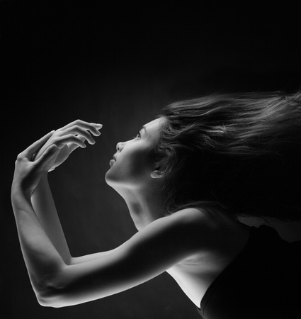 Beauty portrait of woman with flying hair over dramatic black background.