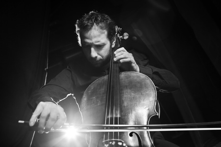 Dramatic portrait of cellist playing classical music on cello on black background. Copyspace. Foto de archivo