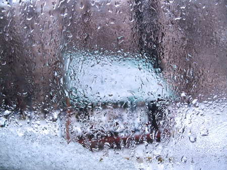View through glass background covered with wet water drops and melting snow. photo
