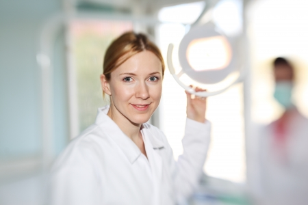 Happy female dentist doctor smiling in camera. Focus on eyes, shallow DOF. Foto de archivo