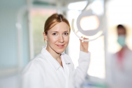 dentista: M�dico dentista femenina feliz sonriente en la c�mara. Centrarse en los ojos, superficial DOF. Foto de archivo