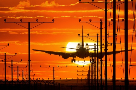 Jet plane departing airport runway over sunset sky background