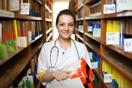 Portrait of female doctor in white lab coat with medical records. photo