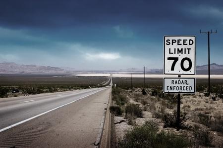 Woestijn snelweg weg naar de horizon met een maximumsnelheid ondertekenen aan een kant.