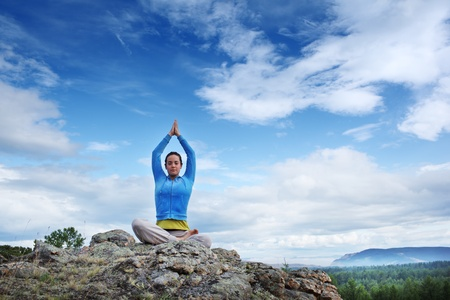 asana: Young woman practicing yoga in lotus pose on top of mountain under blue sky. Copyspace.