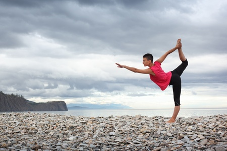 Young woman doing yoga stretch on stone beach at lake Baikal.