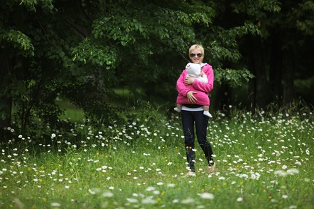 Young mother walking with baby in sling outdoors in park. photo
