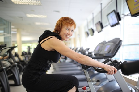 Happy mature woman exercising on a stationary bike in gym.