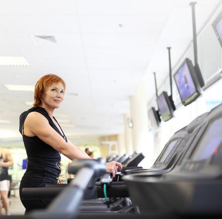 Rijpe vrouw te oefenen op de loopband in de sportschool. Copyspace.