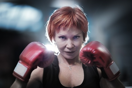Portret van rijpe vrouw in bokshandschoenen kijken naar de camera. Close-up. Stockfoto