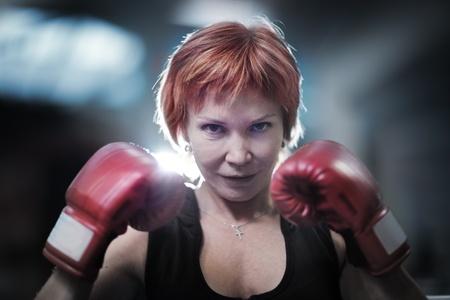 Portrait of mature woman in boxing gloves looking at camera. Closeup. Foto de archivo