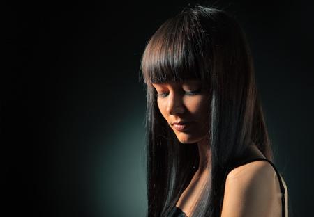 capelli dritti: Ritratto di modello bella con lunghi capelli dritti su sfondo scuro.