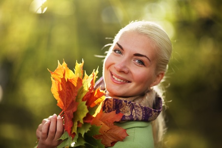 Portrait of happy young woman in autumn park photo