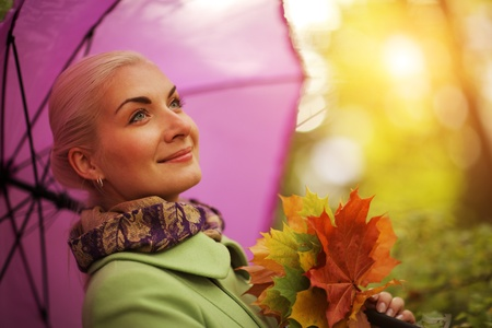 Portrait of happy young woman with umbrella in autumn park photo