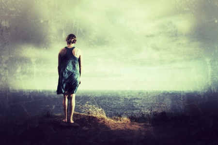 Lonely female standing ontop of a hill looking at ocean vista.