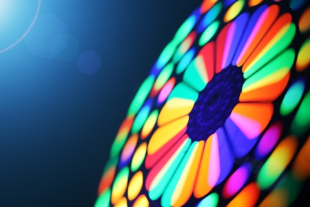 Illuminated colorful spinning wheel, motion blur background.