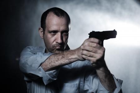 Man aiming pistol gun at night. Closeup.
