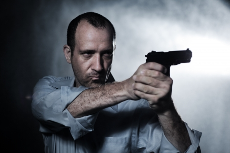 Man aiming pistol gun at night. Closeup. Stock Photo - 10776561