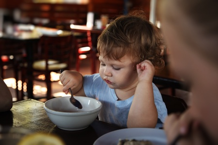 Cute 15 months old baby girl eating in restaurant. Archivio Fotografico