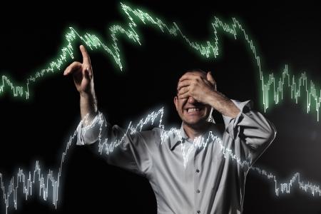 Scared handelaar wijst op de beurs grafieken met gesloten ogen.