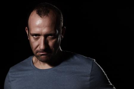 Portret van de boze man op zwarte achtergrond kijkt agressief camera Stockfoto
