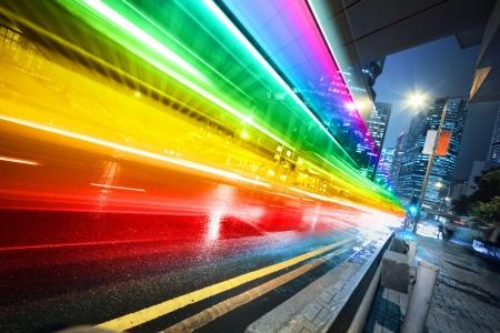 futuristic city: Long exposure shot of blurred bus speeding through night street