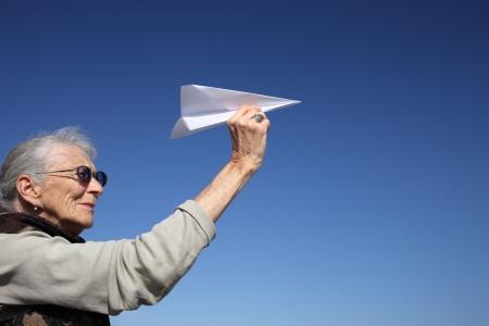 Senior vrouw spelen met papieren vliegtuig over blauwe hemel. Stockfoto