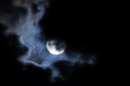Volle maan schijnt door dramatische wolken