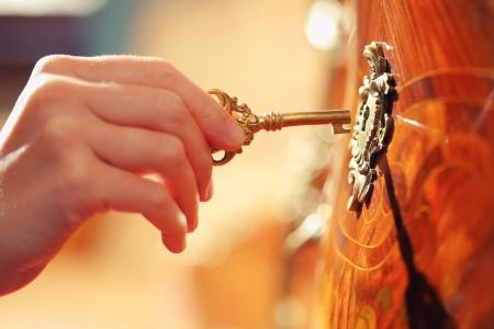 Hand invoegen gouden sleutel in sleutelgat om slot te openen Stockfoto