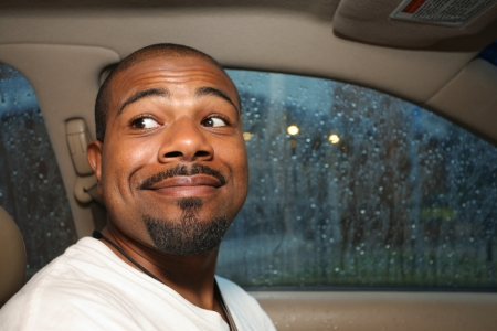 black head and moustache: Cute smiling African American man driving car.
