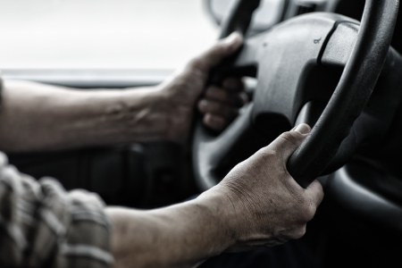 truck driver: Male driver hands holding steering wheel.